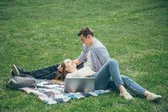 Lycklig man och kvinna som vilar i natur, når att ha lärt royaltyfria foton