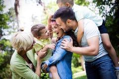 Lycklig man och kvinnlig spela och tyckande om picknick med barn utanför arkivfoto