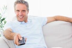 Lycklig man på hans hållande ögonen på tv för soffa Royaltyfri Foto