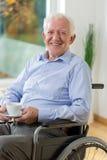 Lycklig man på rullstolen som dricker kaffe Fotografering för Bildbyråer