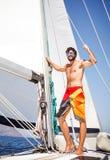 Lycklig man på segelbåten fotografering för bildbyråer