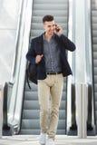 Lycklig man på telefonsamtal vid rulltrappan royaltyfri bild