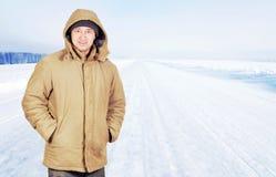 Lycklig man som är utomhus- på en tom väg i vinterdag Fotografering för Bildbyråer