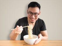 Lycklig man som äter ögonblickliga nudlar royaltyfri bild