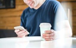 Lycklig man som använder smartphonen i kafé eller hem arkivfoto