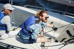 Lycklig man som behandlar segelbåten arkivfoton