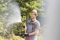 Lycklig man som bevattnar växter på trädgården Fotografering för Bildbyråer