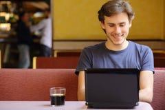 Lycklig man som bläddrar internet på en bärbar dator i en restaurang Royaltyfri Fotografi