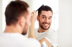 Lycklig man som borstar hår med hårkammen på badrummet royaltyfria bilder