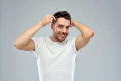 Lycklig man som borstar hår med hårkammen över grå färger Royaltyfria Bilder