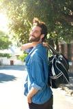 Lycklig man som bort går med lopppåsen Royaltyfri Foto