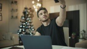 Lycklig man som direktanslutet gör den videopd appellen på mobiltelefonen på jultid stock video