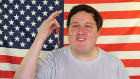 Lycklig man som framme visar hans nya hem- tangent av USA flaggan arkivfilmer