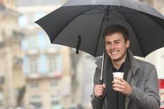 Lycklig man som går rymma en takeaway drink i vinter royaltyfria bilder