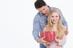 Lycklig man som ger en gåva till hans flickvän ferie Royaltyfri Bild