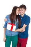 Lycklig man som ger en gåva till hans flickvän Lyckliga unga härliga par som isoleras på en vit bakgrund Fotografering för Bildbyråer