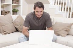 Lycklig man som hemma använder bärbar datordatoren Royaltyfria Bilder