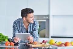 Lycklig man som hemma använder den digitala minnestavlan i kök Royaltyfri Bild