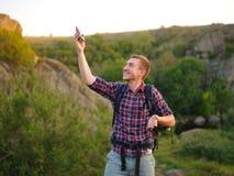 Lycklig man som kallar en telefon på en naturlig bakgrund Turist- student som kallar lyckat en telefon Bra anslutningsbegrepp Royaltyfri Bild