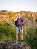 Lycklig man som kallar en telefon på en naturlig bakgrund Turist- student som kallar lyckat en telefon Bra anslutningsbegrepp Fotografering för Bildbyråer