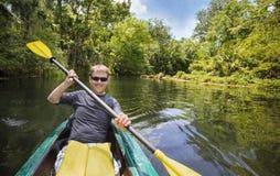 Lycklig man som Kayaking ner den härliga djungelfloden arkivfoton