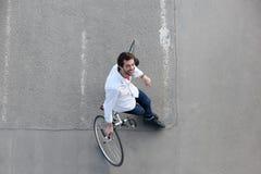 Lycklig man som kopplar av med cykeln på gatan Fotografering för Bildbyråer