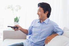 Lycklig man som kopplar av på hållande ögonen på tv för soffa royaltyfria foton