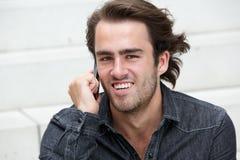 Lycklig man som ler med mobiltelefonen Arkivfoto