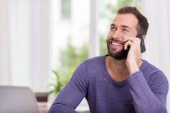 Lycklig man som ler, som han pratar på hans smartphone Arkivbild