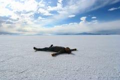 Lycklig man som ligger på yttersidan av Salar de Uyuni, Bolivia Royaltyfri Fotografi