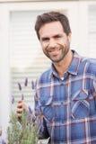 Lycklig man som luktar hans lavendelväxt Royaltyfri Bild