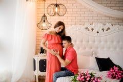 Lycklig man som lyssnar till hans härliga gravida mage för fru` s royaltyfri fotografi