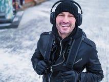 Lycklig man som lyssnar till musik från en smart telefon med en bakgrund för värmesolnedgångstad Arkivbild