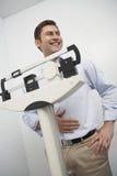 Lycklig man som mäter vikt på vägningsskala Fotografering för Bildbyråer