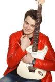 Lycklig man som omfamnar hans vita elektriska gitarr Fotografering för Bildbyråer