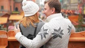 Lycklig man som omfamnar le kvinnan på julmarknadsbakgrund Förälskat samtal för par om något som ser på arkivfilmer