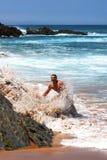 Lycklig man som plaskas av en våg på stranden Arkivfoto