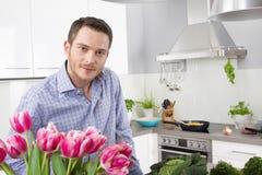 Lycklig man som poserar i köket med rosa tulpan royaltyfria foton