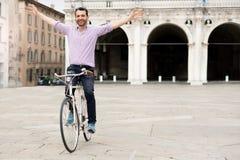 Lycklig man som rider hans cykel i staden royaltyfri bild