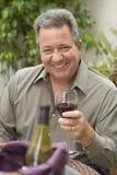 Lycklig man som rymmer ett exponeringsglas av Wine Arkivfoto