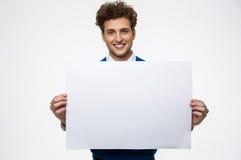 Lycklig man som rymmer tomt papper arkivfoto