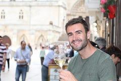 Lycklig man som rymmer vitt vin royaltyfria bilder