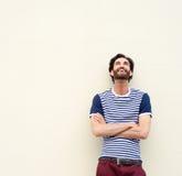 Lycklig man som skrattar med korsade armar och ser upp Royaltyfri Fotografi