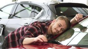 Lycklig man som slår hans nya bil som försiktigt ler upp visningtummar på återförsäljaren royaltyfri fotografi
