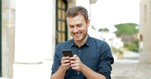 Lycklig man som smsar på mobiltelefonen i gatan