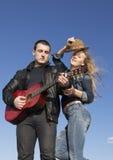 Lycklig man som spelar den akustiska gitarren med kvinnan som som av tar hennes hatt Arkivbilder