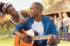 Lycklig man som spelar den utomhus- gitarren arkivbilder