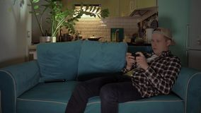 Lycklig man som spelar leken på hans mobil, medan ligga på soffan 4K arkivfilmer