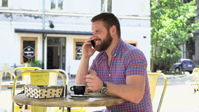 Lycklig man som talar vid smarphone under frukosten i kafé stock video