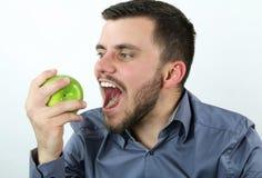 Lycklig man som äter ett grönt äpple Arkivbild